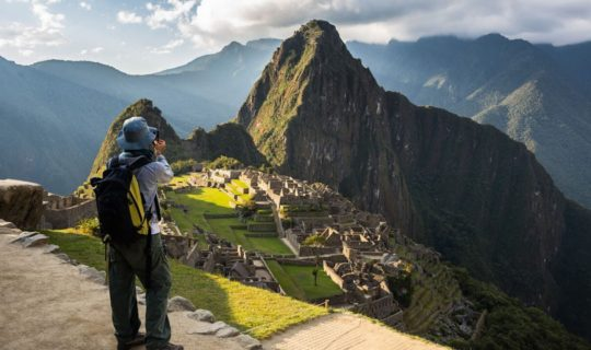 man-standing-on-cliff-overlooking-machu-picchu