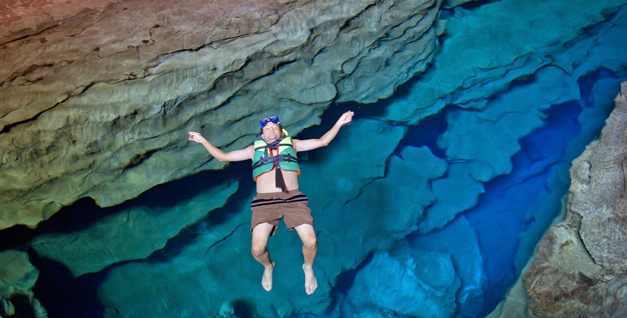 man floating in blue cave
