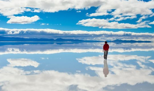 man-standing-on-water-filled-uyuni-salt-flats-in-bolivia