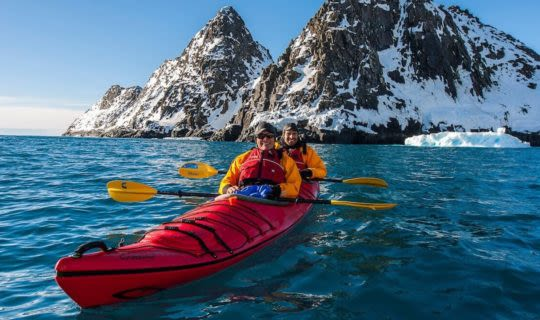 kayakers-in-antarctica-with-glacier-in-background