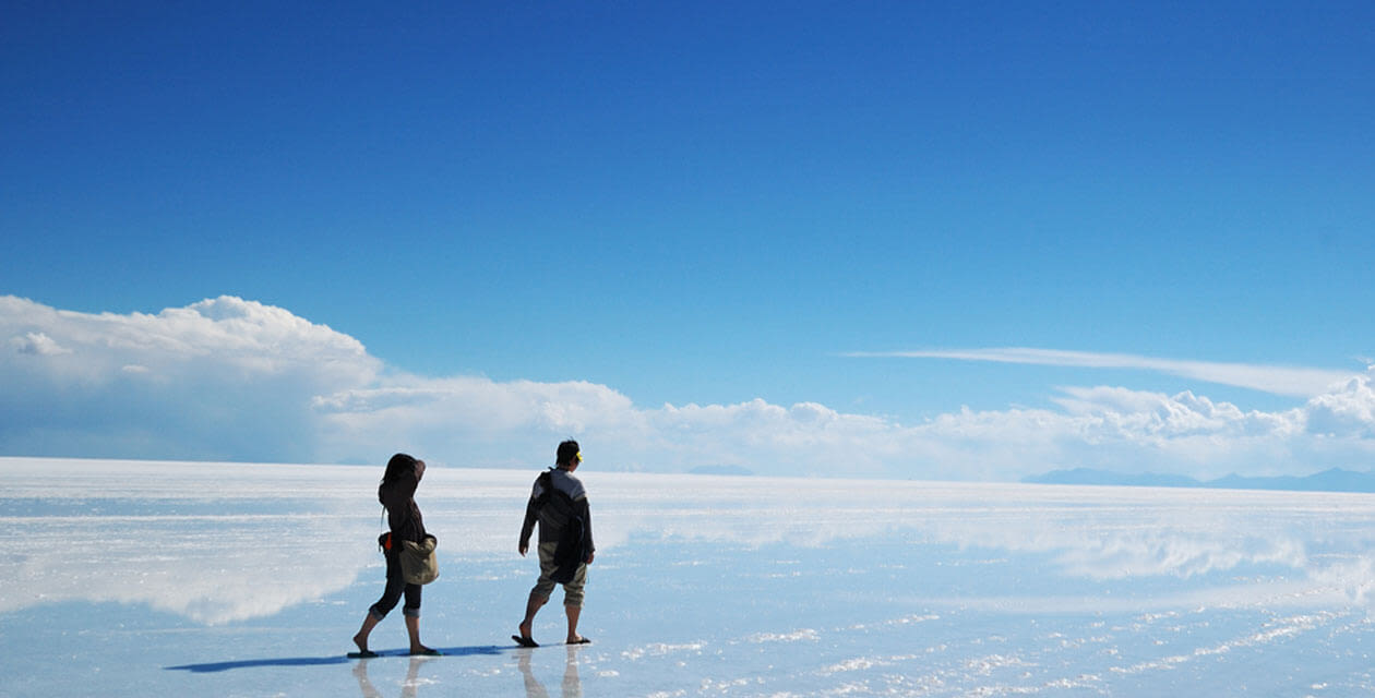couple walking on Salinas Grandes - a salt flat in salta