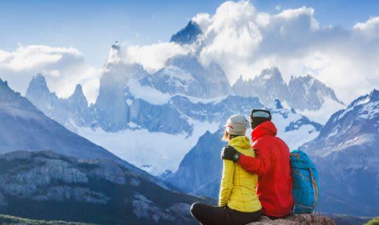 couple-cuddling-on-mountain-top-enjoying-views