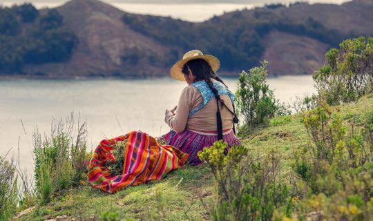 Native woman of Bolivia sitting by lake