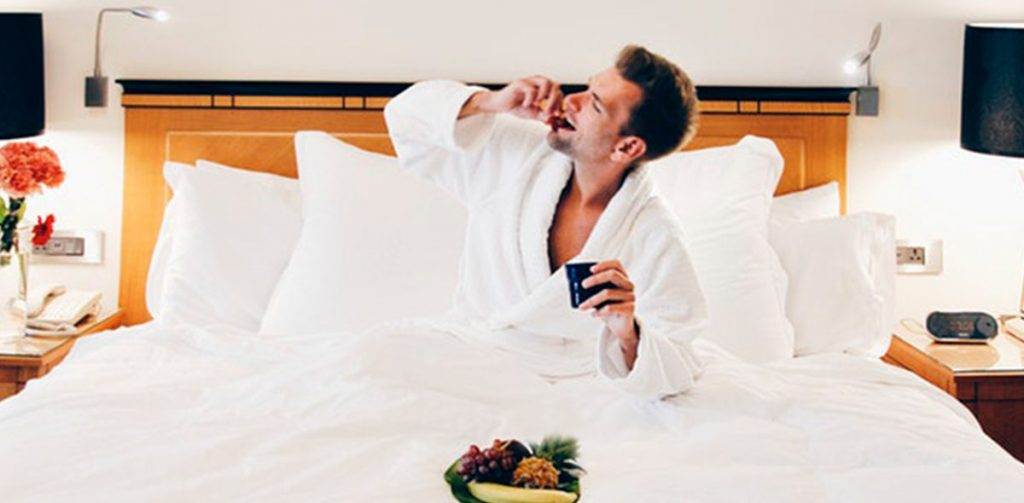man enjoying room service in bed