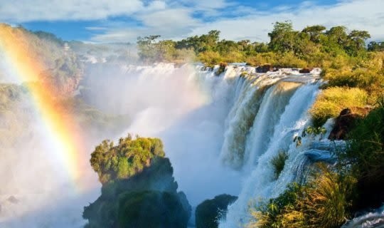 The rushing Iguazu Falls and a rainbow