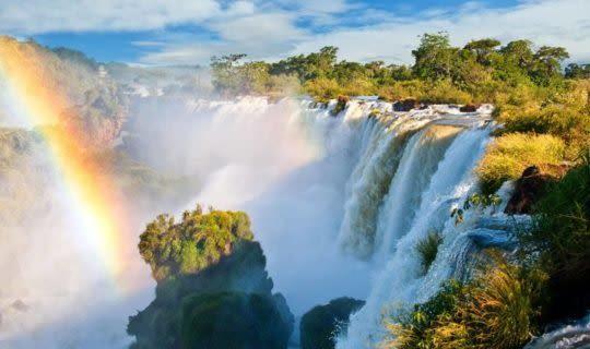 The rushing Iguazu Falls and a rainbow