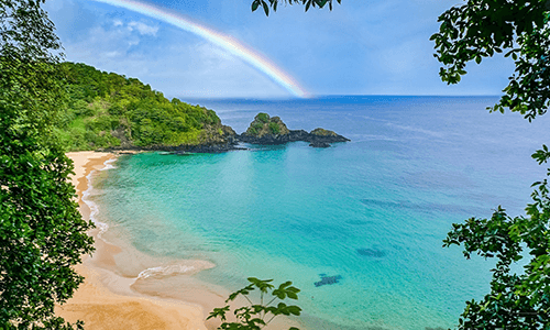 Beach in Brazil with sun and a rainbow