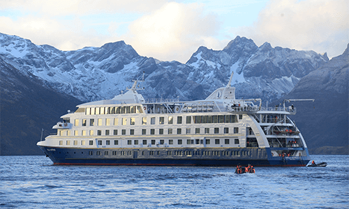 A cruise ship sails through the water with gorgeous mountains in the background