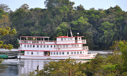 The Tucano River Cruise sails through the river, with lush trees surrounding