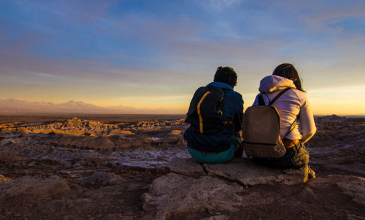 two travelers watching sunrise over desert