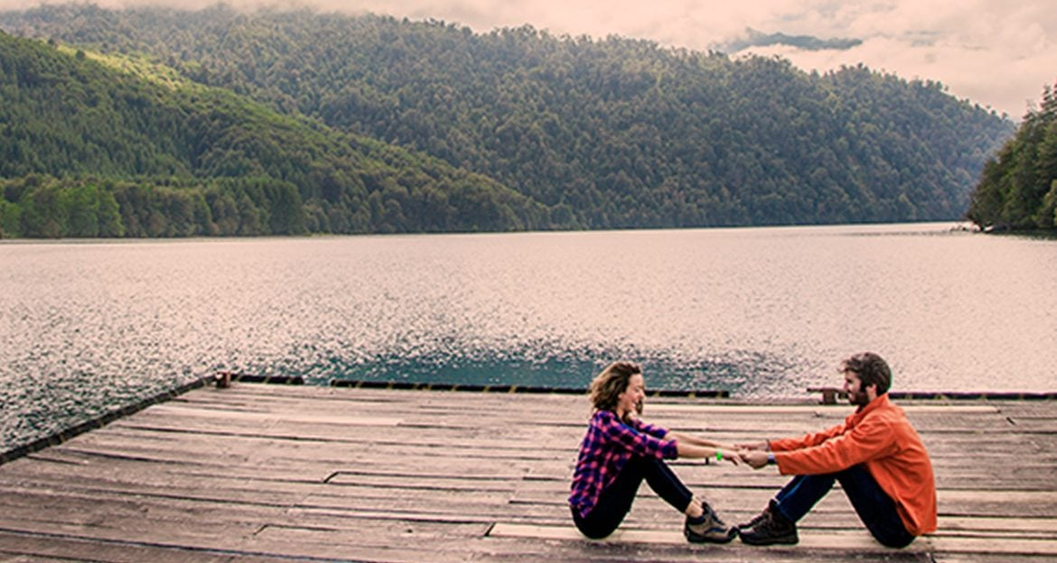 couple-relaxing-and-holding-hands-on-serene-dock-over-lake