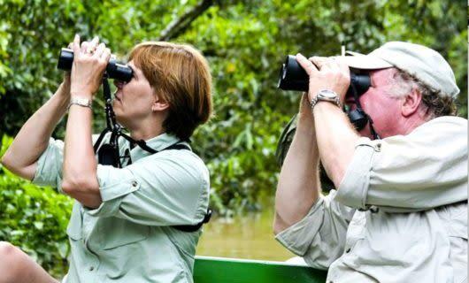 Two travelers on Amazon boat use binoculars
