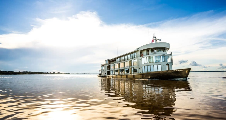 Delfin cruise moves across Amazon river at low sun