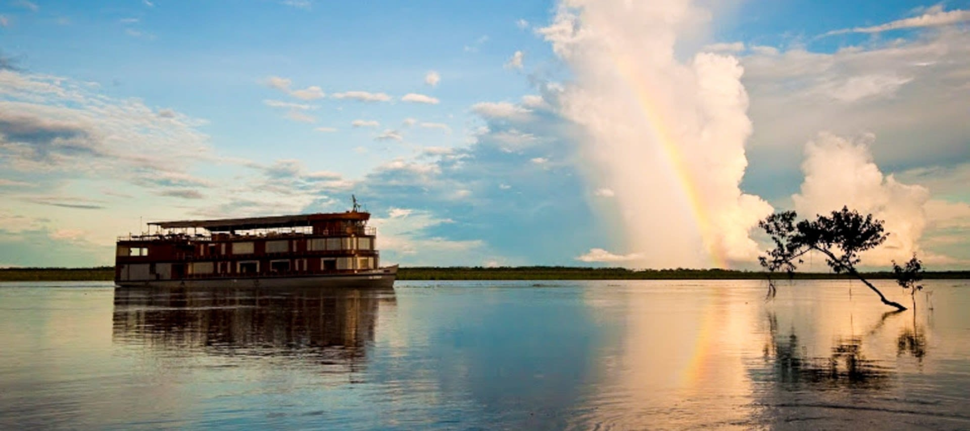 River cruise boat on Amazon with rainbow
