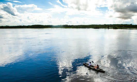 Travelers kayak on the Amazon River