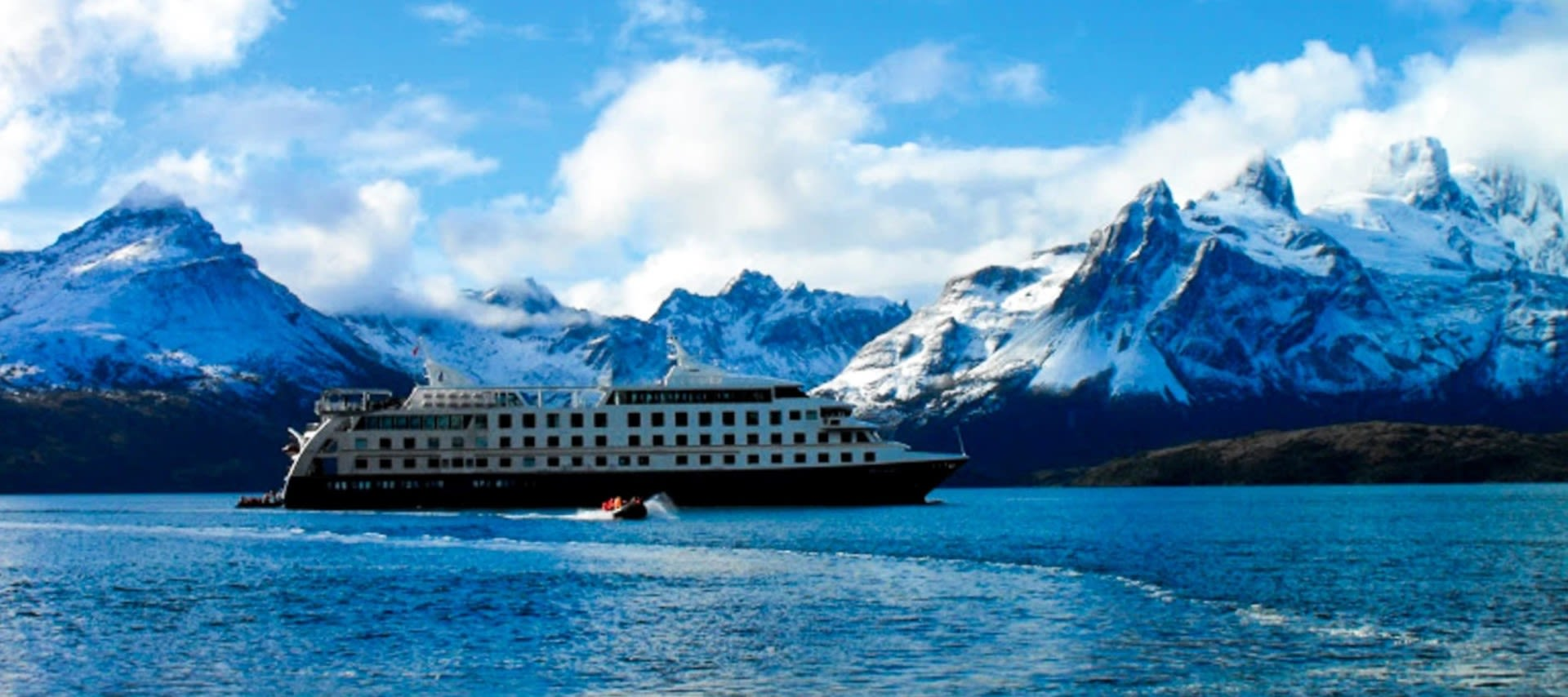 Argentina Cruise ship in front of mountains in Patagonia
