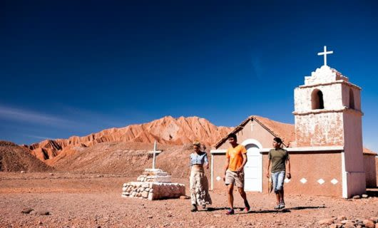 Travelers walk past small building in Atacama Desert