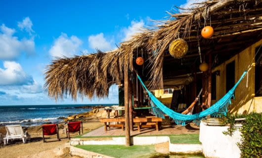 Straw-roofed building on beach with blue hammock