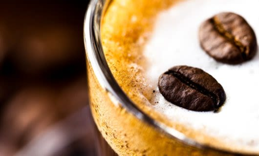 Coffee beans float on top of coffee foam