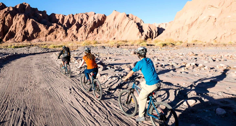Cyclists ride near desert mountains