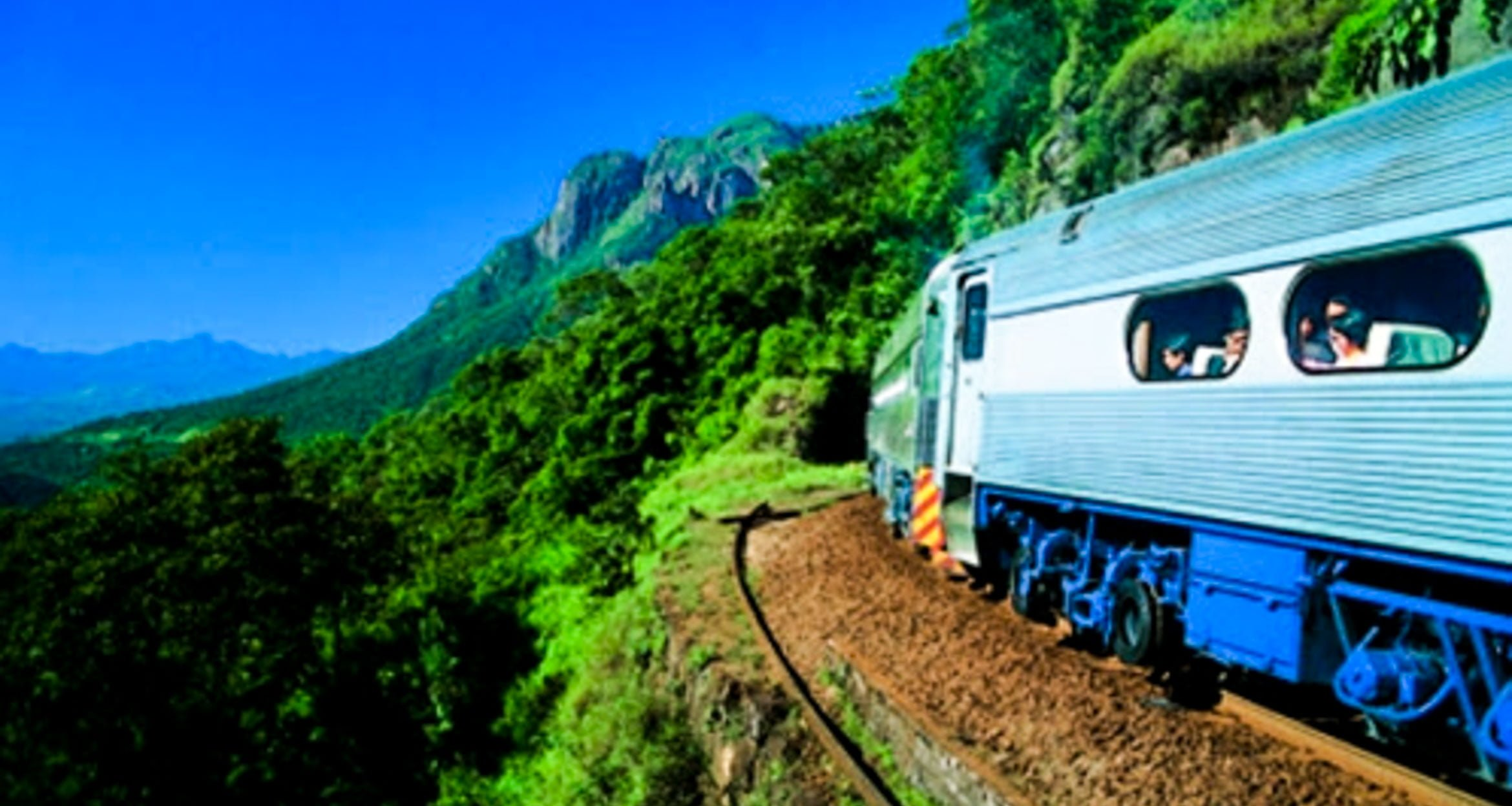 Blue train runs along railway in Brazil forest