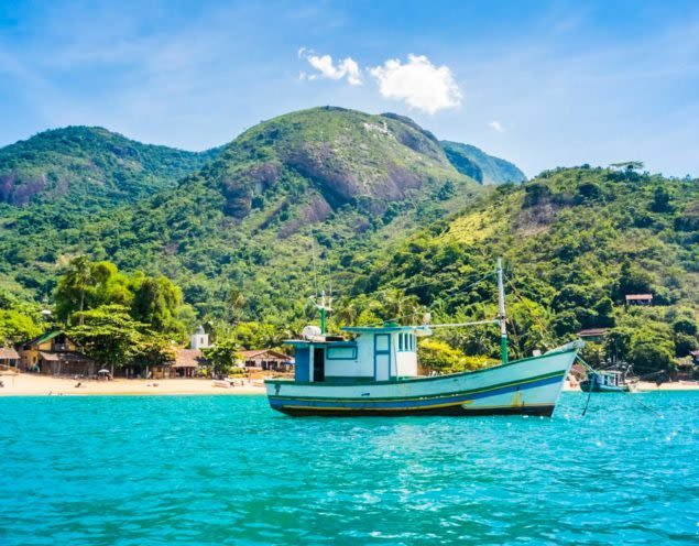 Boat anchored near shore in front of mountain