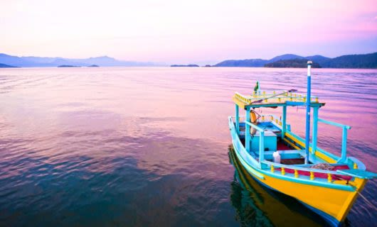 Colorful boat on calm purple waters at sunset