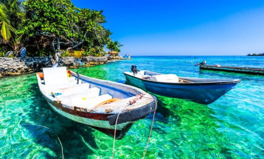 Boats anchored on clear blue water