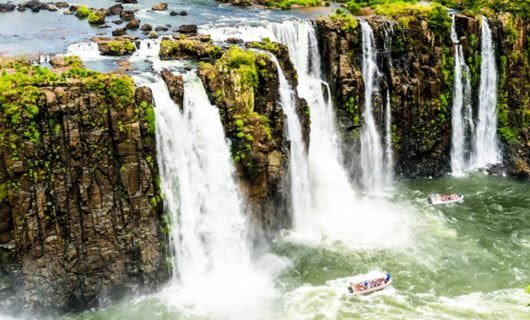 Boats full of tourists below Iguazu Falls