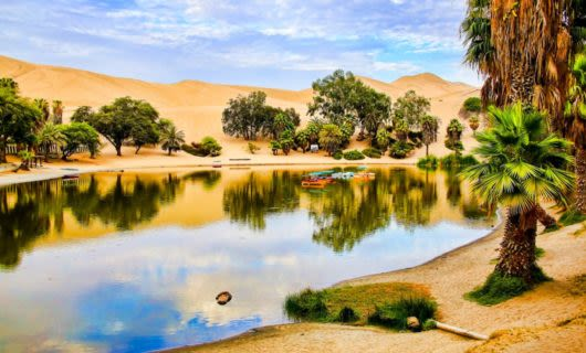 Boats sit on surface of desert oasis