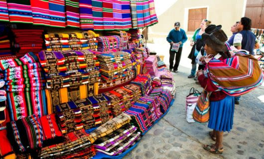 Woman looks at colorful cloth in Bolivia market
