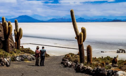 Travelers stand in road leading to Bolivia salt flats