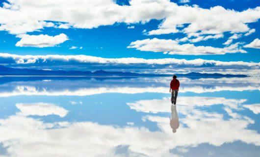 Person walks across reflective salt flats