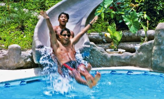 Two boys exit waterslide