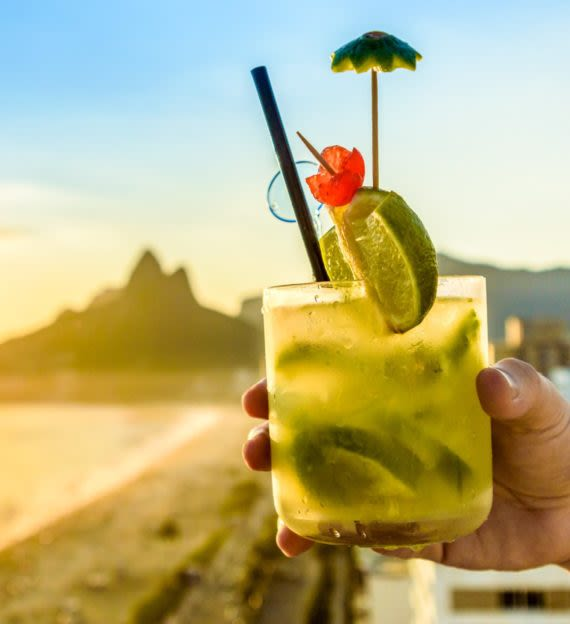 Hand holds cocktail on Brazil beach