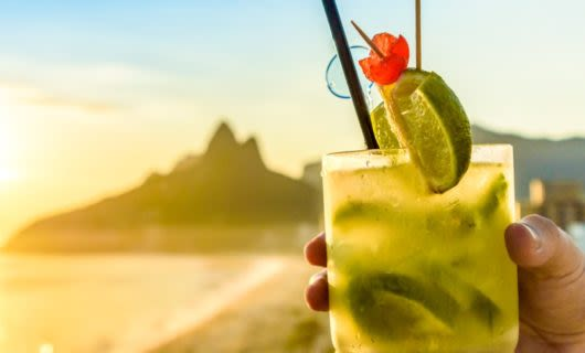 Hand holds cocktail on Brazil beach