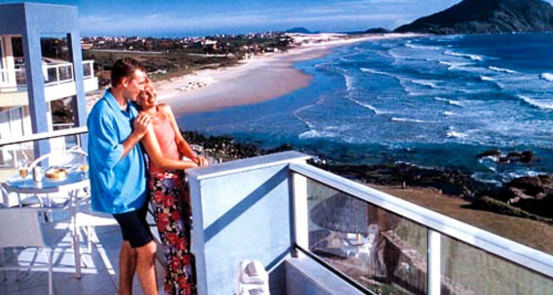 Couple stands on balcony of Costao Santinho Resort
