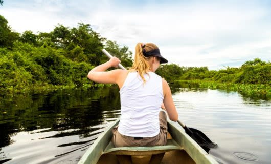 Woman paddles canoe down South America river