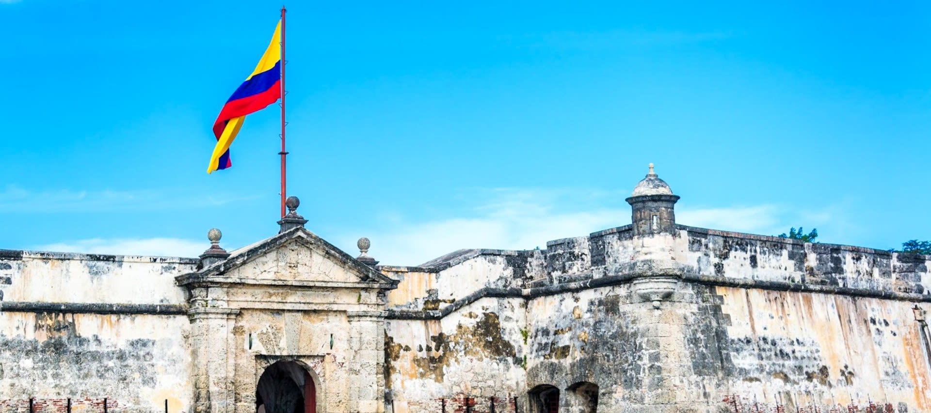 Colorful flag on top of Cartagena fortress wall. One of the many things to do in cartagena