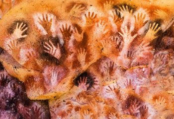 Colorful handprints painted on the inside of a cave wall in Patagonia