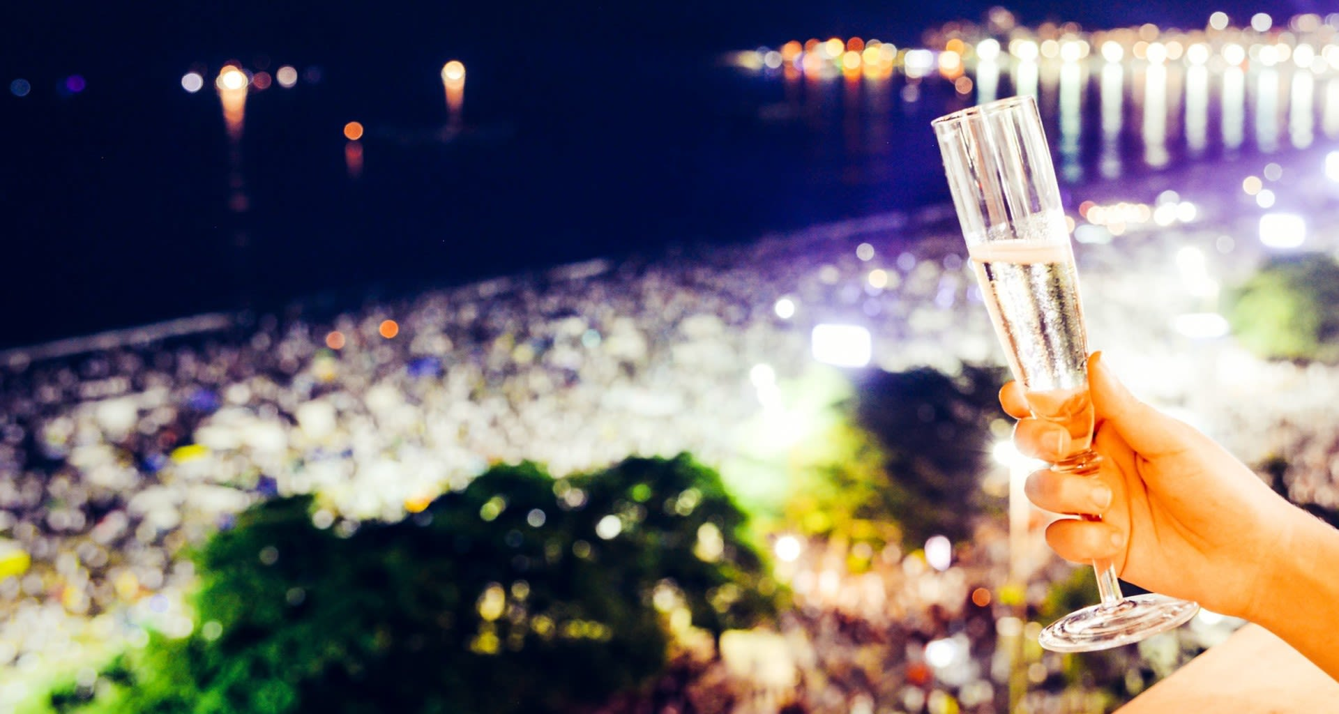 Hand holds out champagne flute at night in Rio de Janeiro
