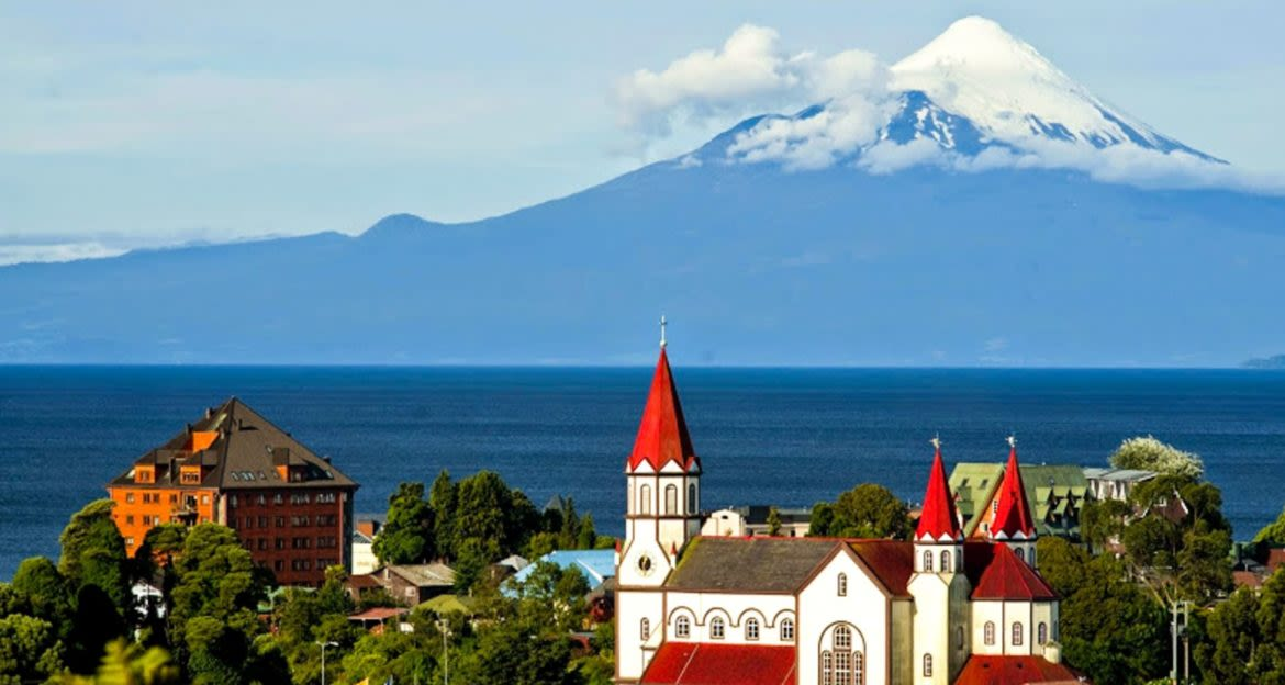 Red-roofed building in Chile city in front of mountain