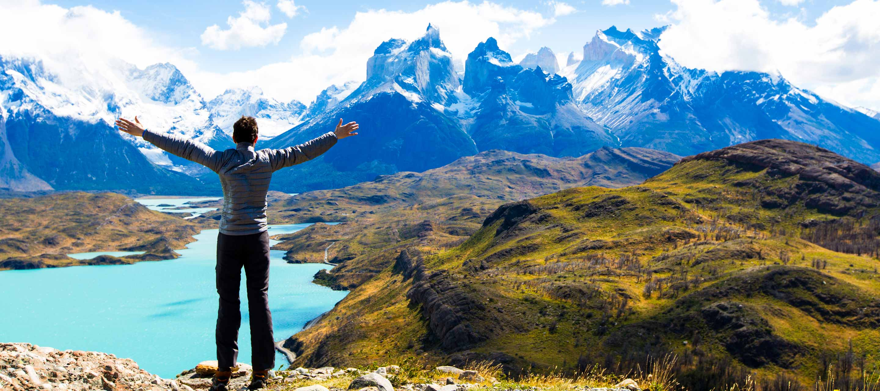 Hiker stands against Torres del Paine on a Chile tour mountains