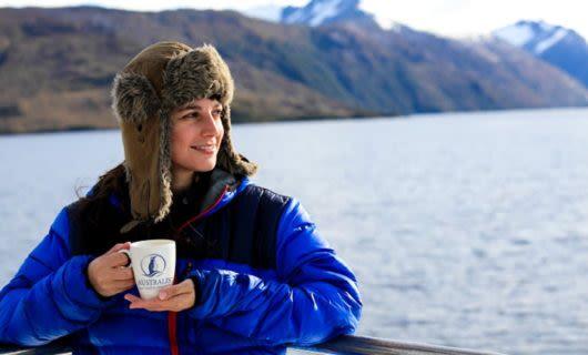 Traveler enjoys a mug of coffee on Australis cruise ship