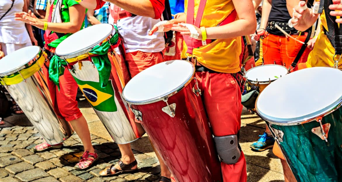 Group of performers play colorful drums