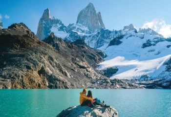 Couple sitting on rock at Torres del Paine National Park Chile