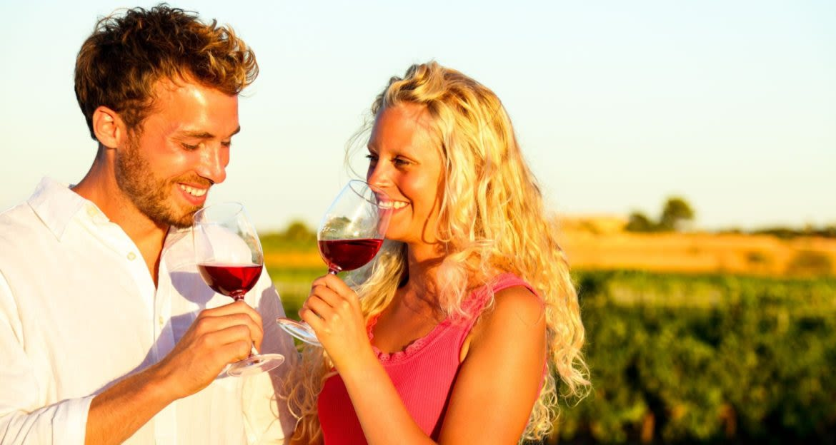 Couple drinks red wine in South America vineyard