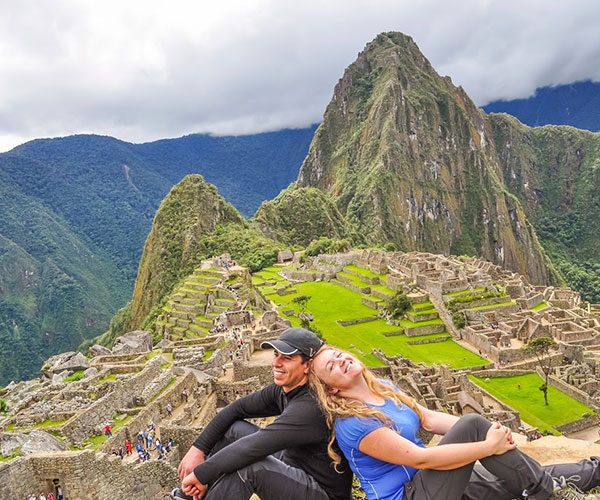 cute couple sitting over ledge at Machu Picchu taking in view