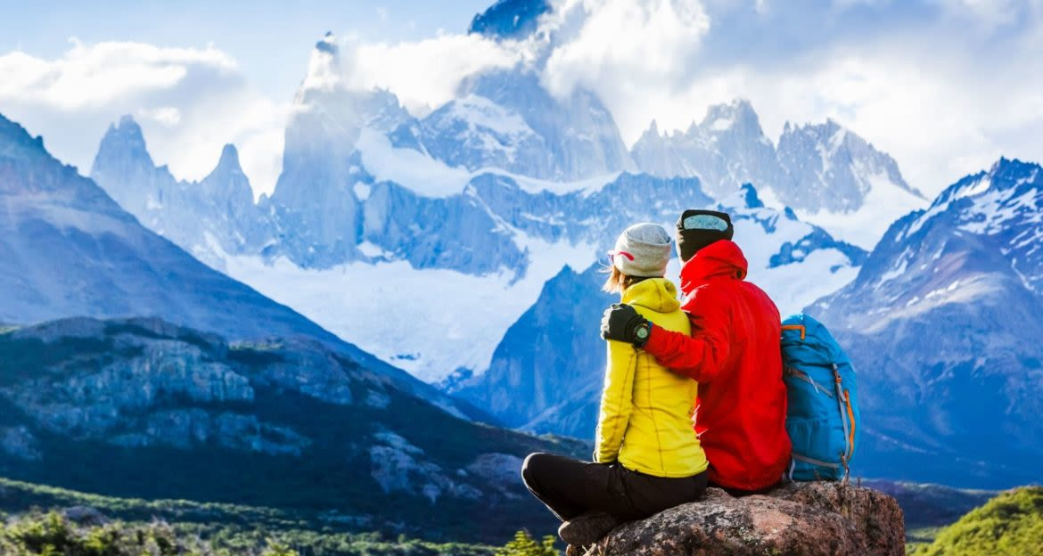 Couple sits on rock overlooking Torres del Paine