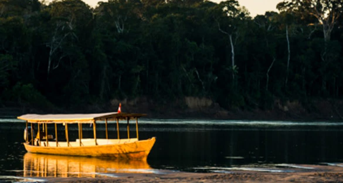 Covered boat sits on beach of river